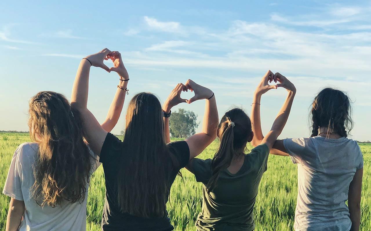 Ungdomar som formar hjärtan med händerna