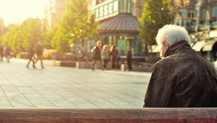 Att höra till - äldre man på en parkbänk