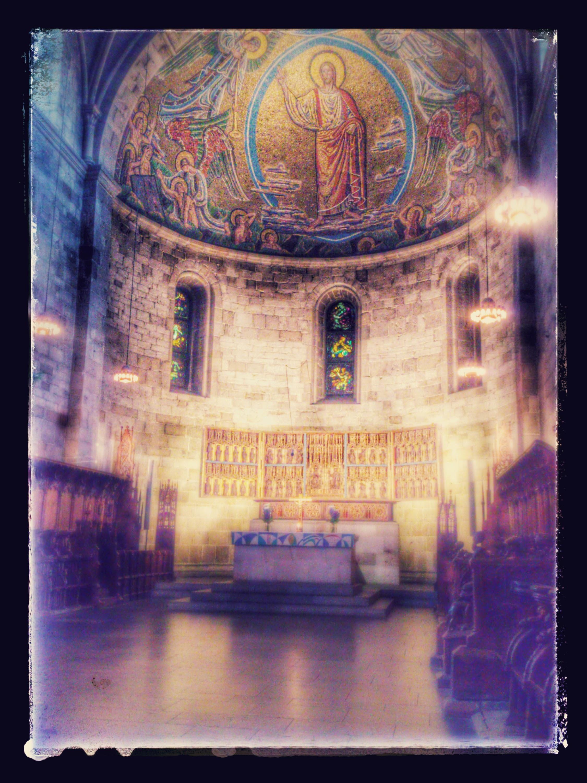 Koret i en kyrka upplyst av stearinljus. En medeltida fresk i välvda taket föreställer Jesus.