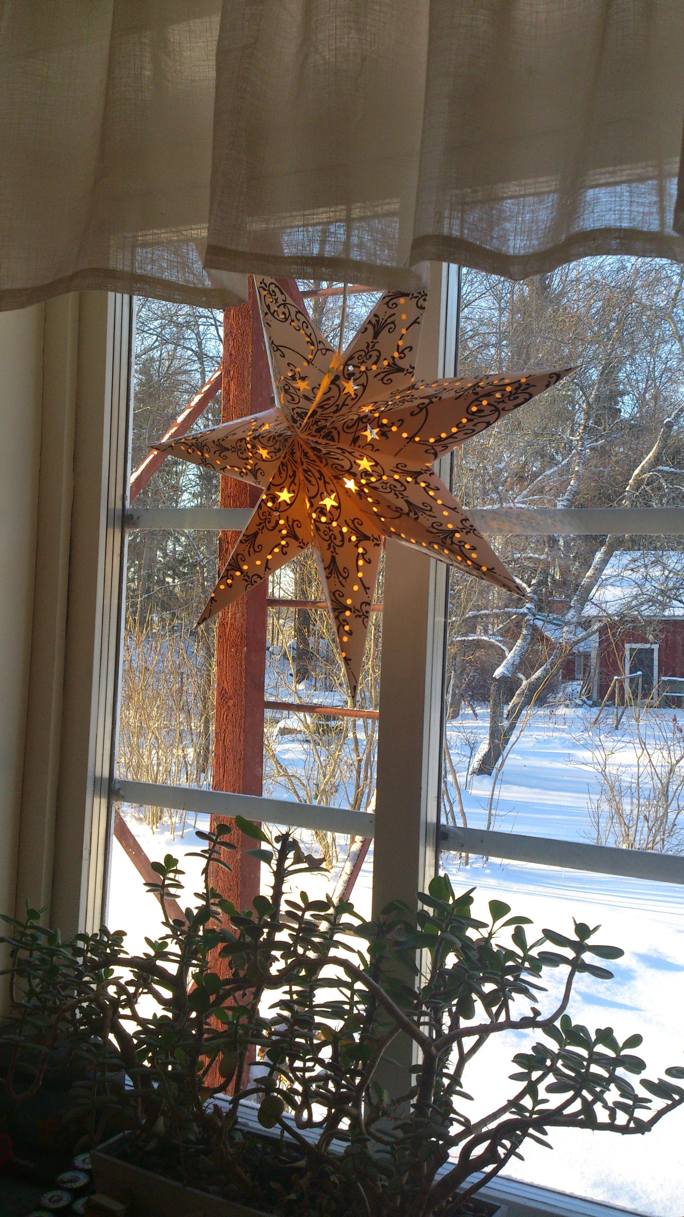 En adventsstjärna i ett fönster. Ute är det snö.